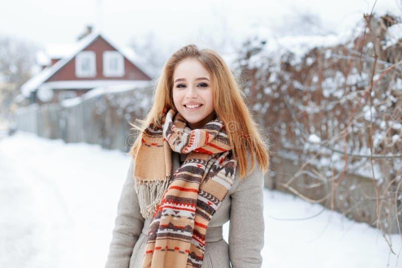 Nette junge blonde Frau mit einem schönen Lächeln und einem natürlichen Make-up in einem grauen Wintermantel mit einem woolen Sch lizenzfreie stockfotos