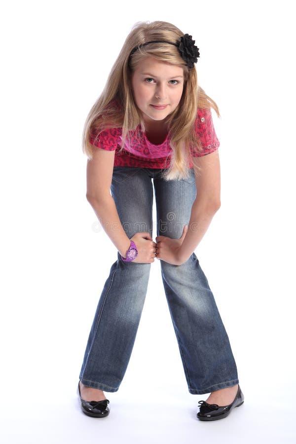 Nette junge blonde Schulemädchenjeans und rosafarbenes Hemd stockfotos