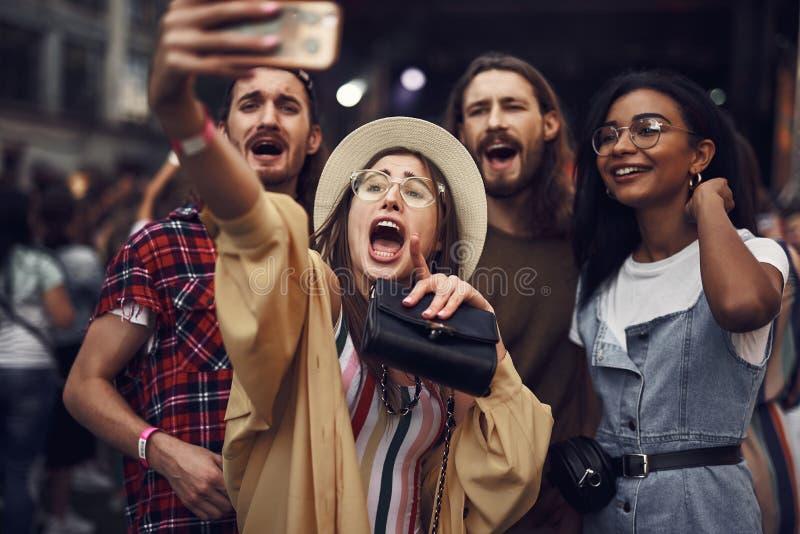 Nette junge Dame in den Gläsern, die selfie mit Freunden nehmen stockbilder
