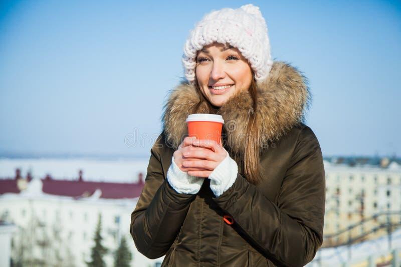 Nette junge Dame mit dem coffe, zum an einem sonnigen eisigen kalten Wintertag zu gehen stockbilder