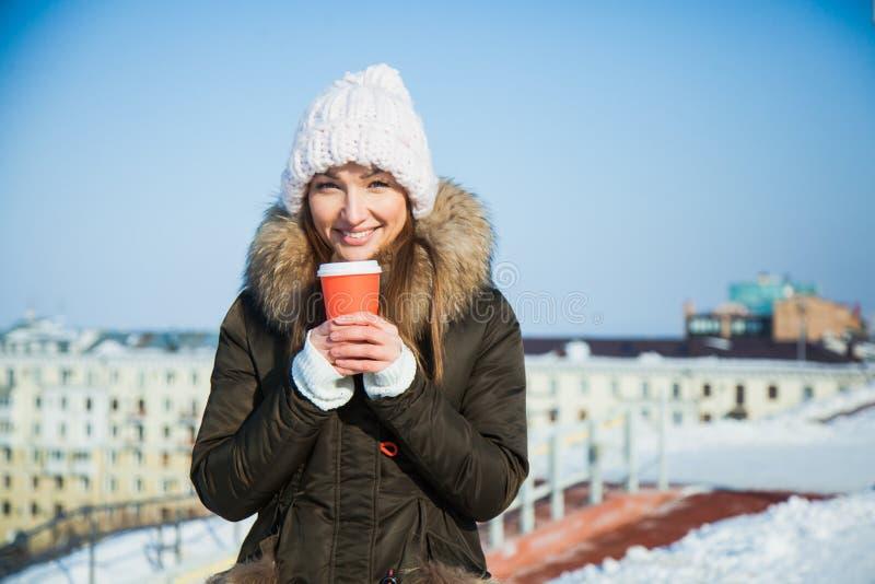 Nette junge Dame mit dem coffe, zum an einem sonnigen eisigen kalten Wintertag zu gehen lizenzfreies stockfoto