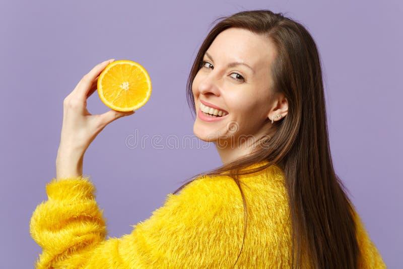 Nette junge Frau in der Pelzstrickjacke, die in der Hand Hälfte der frischen reifen orange Frucht lokalisiert auf violettem Paste lizenzfreie stockbilder