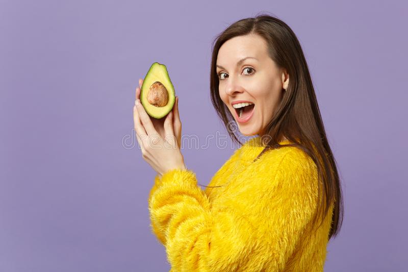 Nette junge Frau in der Pelzstrickjacke, die offene haltene Hälfte des Munds der frischen reifen grünen Avocado lokalisiert auf V lizenzfreie stockfotos