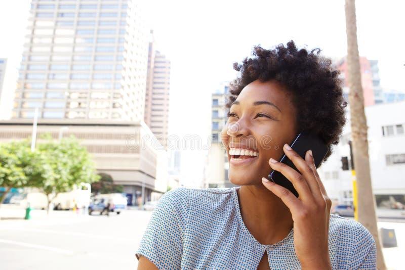 Nette junge Frau in der Stadt, die ein Telefon cal herstellt lizenzfreies stockbild