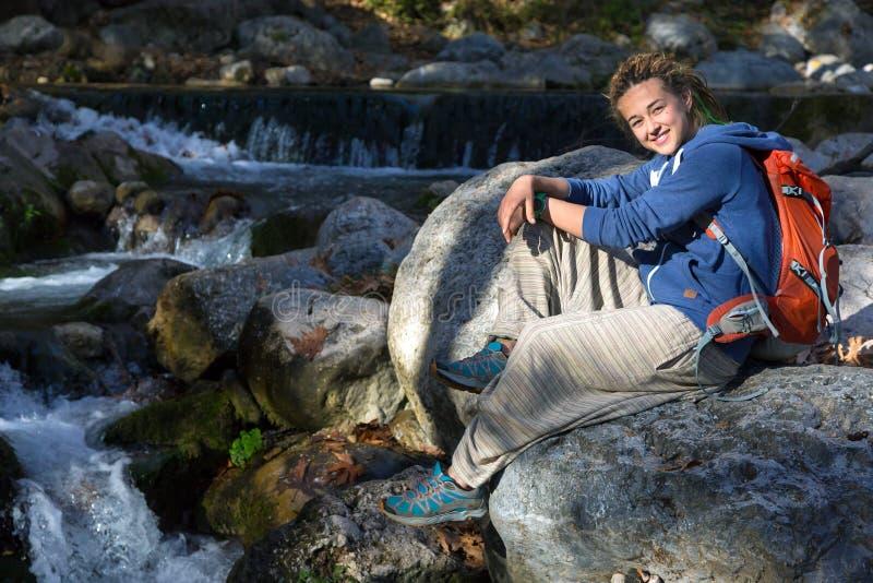Nette junge Frau, die auf dem nahen Gebirgsbach-Steinc$lächeln sitzt stockbild