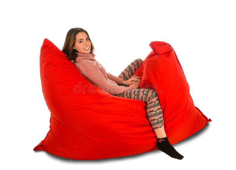 Nette junge Frau, die auf dem roten Sitzsacksofastuhl an lokalisiert sitzt stockbilder