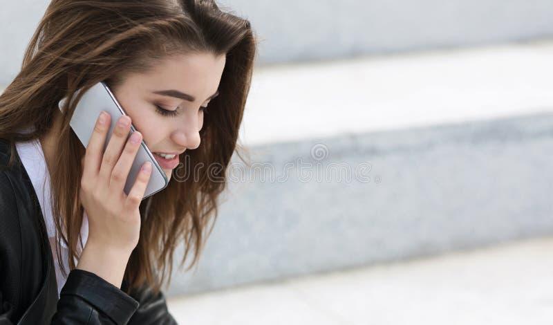 Nette junge Frau, die draußen auf Smartphone spricht lizenzfreies stockfoto