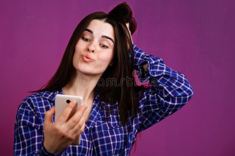 Nette junge Frau, die ein selfie macht stockbild