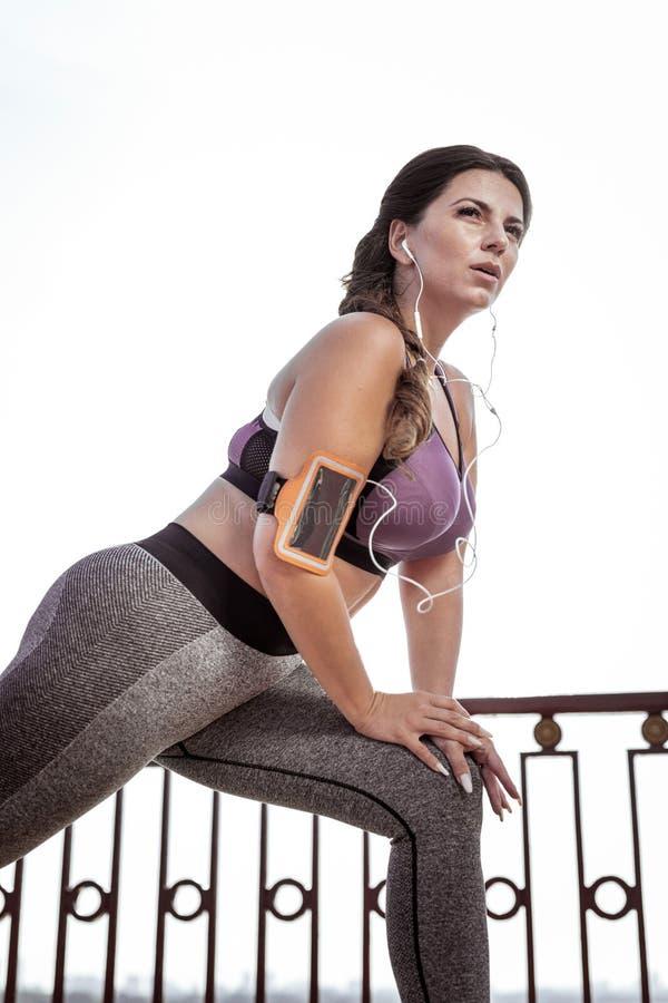 Nette junge Frau, die eine Morgengymnastik tut stockbilder