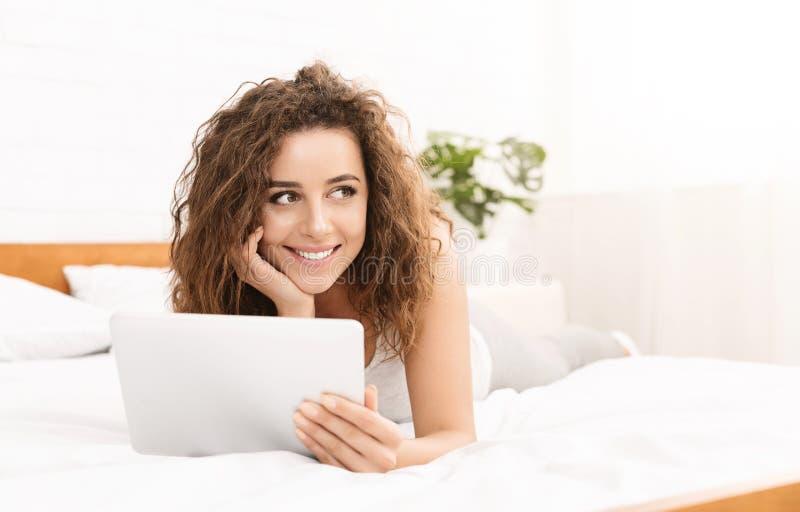 Nette junge Frau, die im Bett mit Tablette liegt lizenzfreies stockfoto