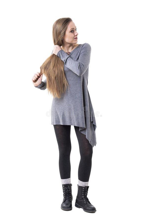 Nette junge Frau, die langes gesundes Haar als tägliches Programm weg schaut hält und bürstet stockfoto