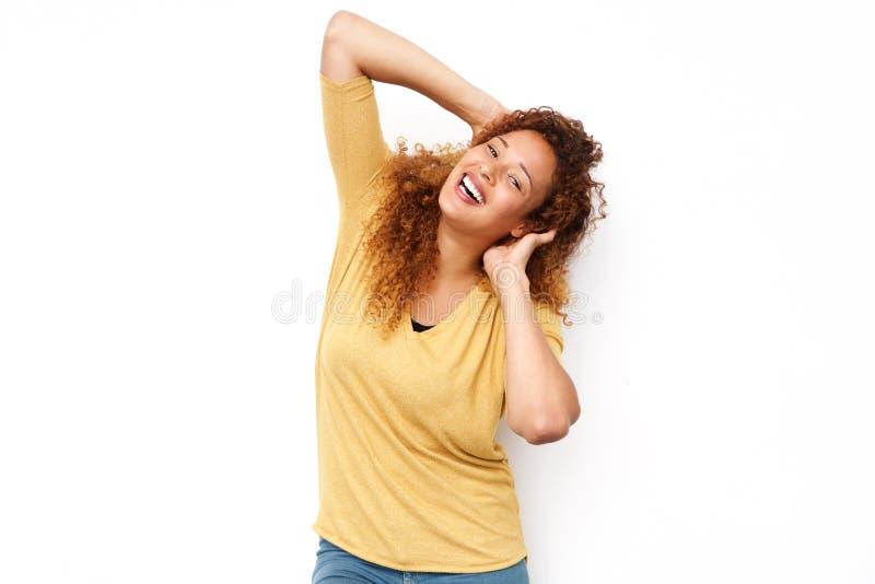Nette junge Frau, die mit den Händen im Haar gegen lokalisierten weißen Hintergrund lacht lizenzfreies stockfoto