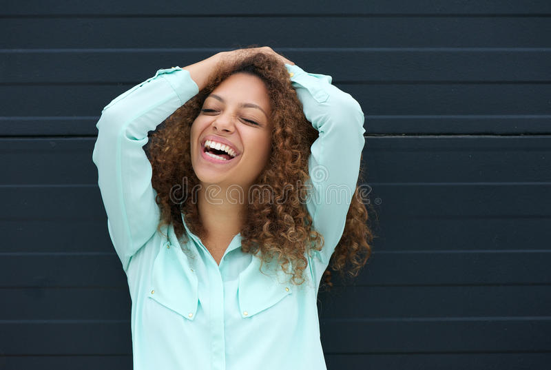 Nette junge Frau, die mit glücklichem Ausdruck lacht stockfotografie