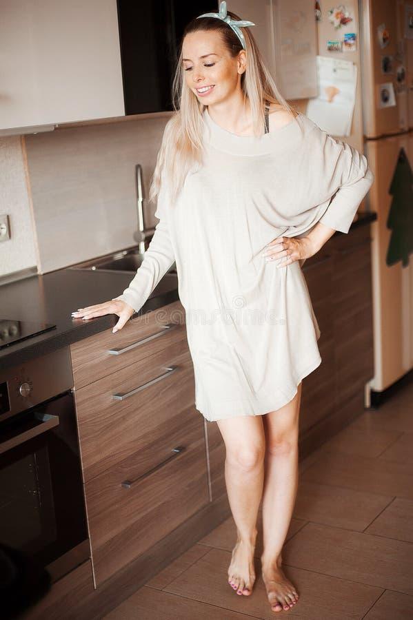 Nette junge Frau, die nahen Schreibtisch in der Küche steht Konzept des häuslichen Komforts Lächelnde langhaarige Hausfrau stockbilder