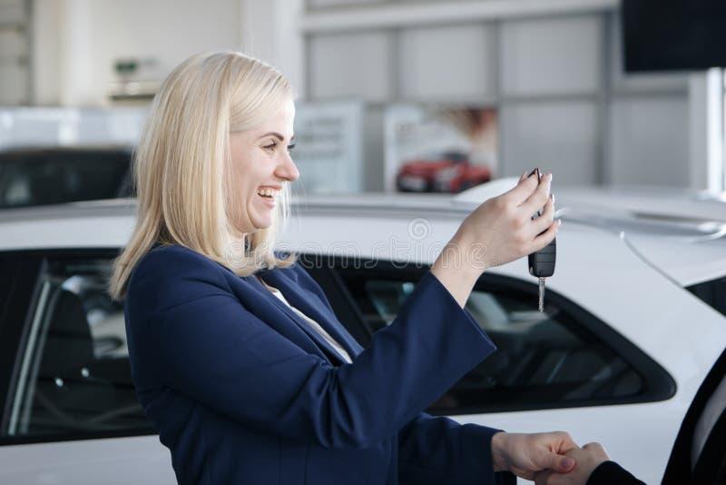 Nette junge Frau, die Neuwagenschlüssel im Autoshop empfängt stockfoto