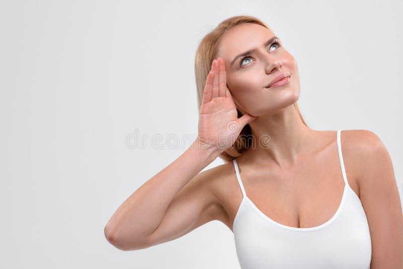 Nette junge Frau, die versucht, etwas zu hören stockfoto