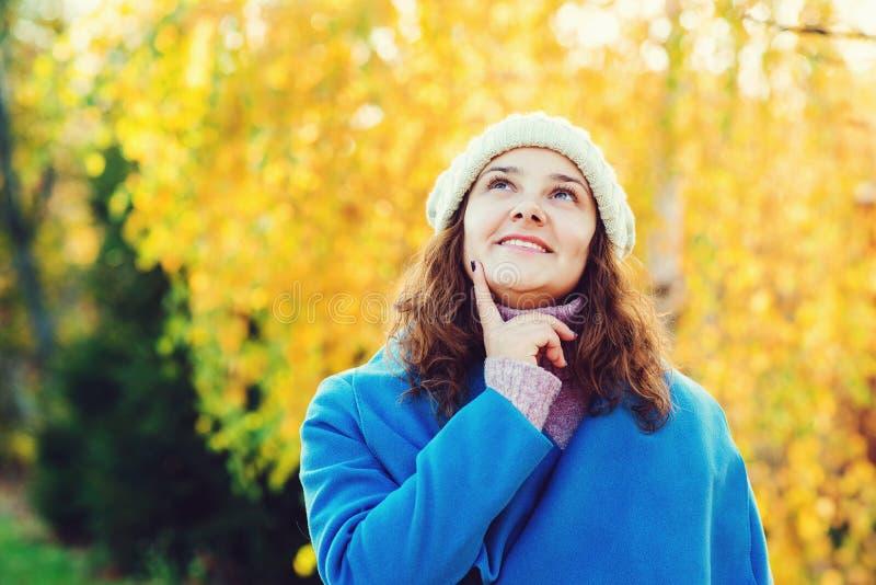 Nette junge Frau, die warmen Mantel und Strickmütze trägt Herbstfrauenmode, Kopienraum M?dchen, das in Herbstpark geht emotional lizenzfreie stockfotografie