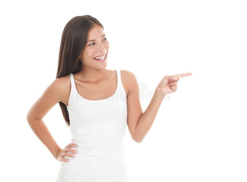 Nette junge Frau, die zur Seite zeigt und schaut lizenzfreies stockfoto