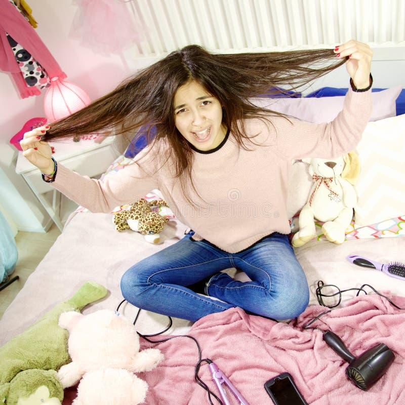 Nette junge Frau in ihrem Schlafzimmer schreiend für unordentliches Haar lizenzfreies stockfoto