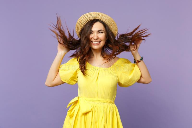 Nette junge Frau im gelben Kleid, ausgebreitete Hände des Sommerhutes mit dem flüssigen Haar, die Kamera schauend lokalisiert auf stockfotos