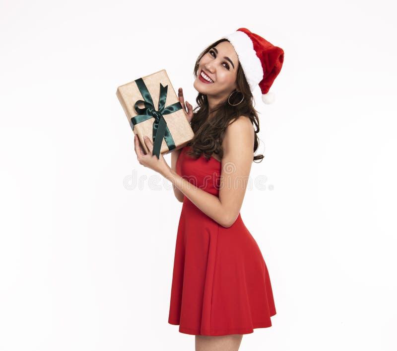 Nette junge Frau im roten Kleid Sankt, die Geschenkbox hält lizenzfreie stockfotografie