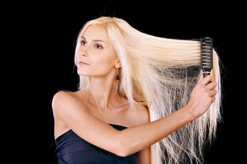 Nette junge Frau kämmt Haar stockbild