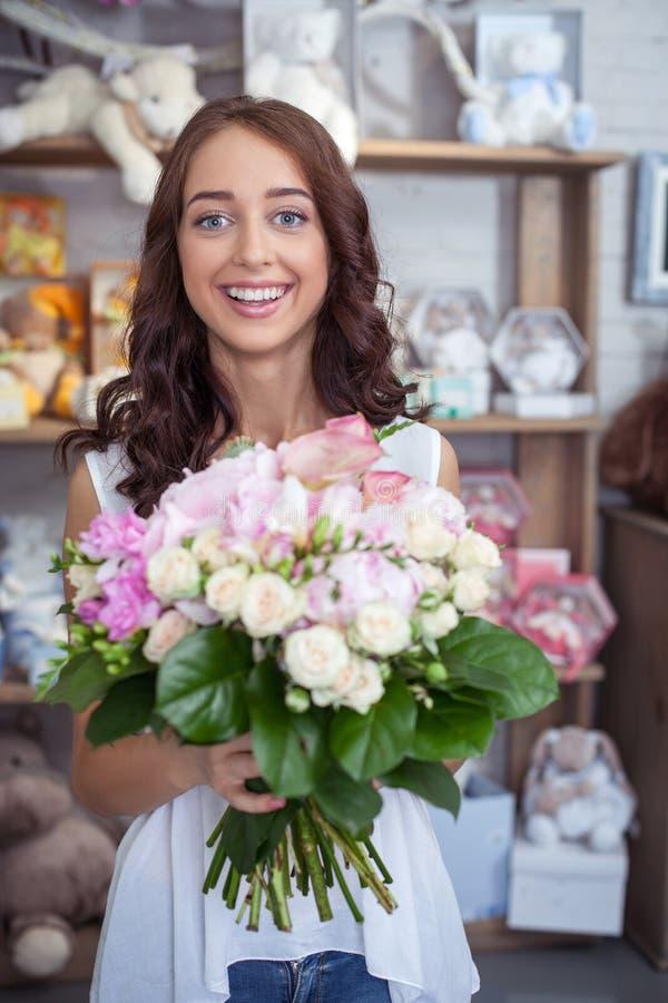 Nette junge Frau kauft Blumenstrauß in der Blume stockbilder
