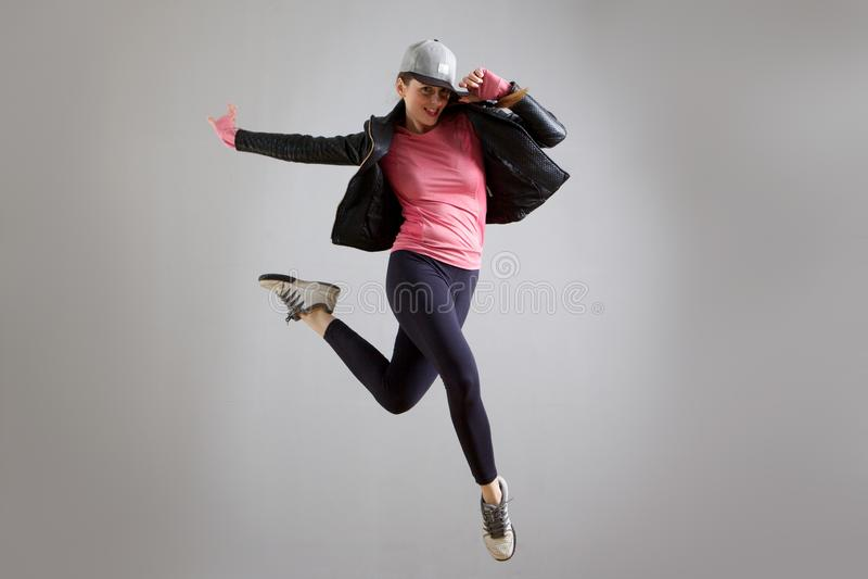 Nette junge Frau mit dem Hut, der in die Luft gegen grauen Hintergrund springt stockbilder