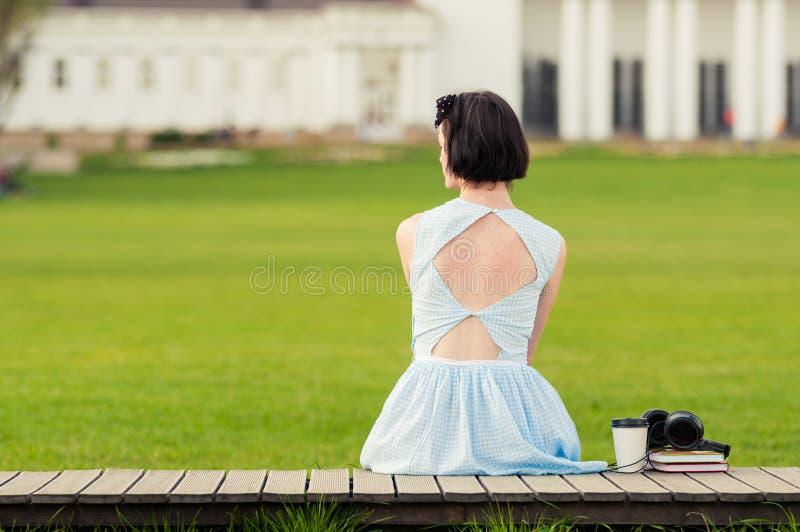Nette junge Frau mit dem Weinlesekleid, das im Park steht lizenzfreies stockbild