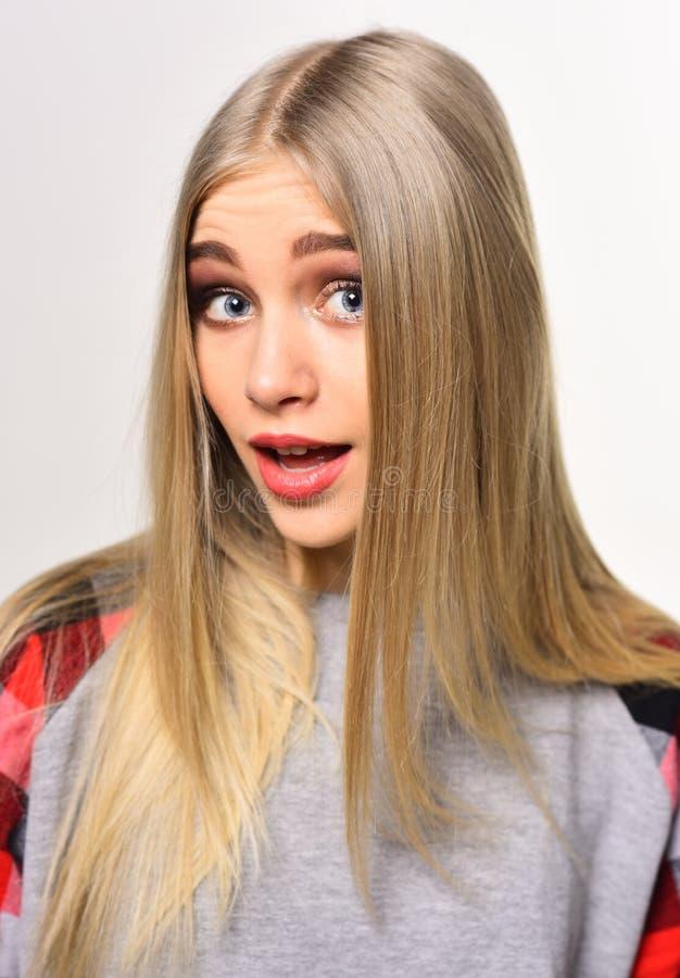 Nette junge Frau mit starken Augenbrauen und langen blonden glänzenden dem Haar, die im Studio lokalisiert auf weißem Hintergrund lizenzfreies stockbild
