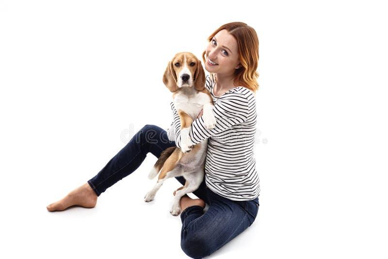 Nette junge Frau umfasst ihren Hund lizenzfreies stockbild