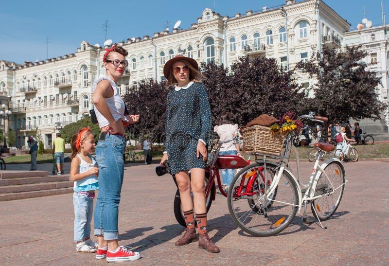 Nette junge Frauen in der Weinlesekleidung sprechend vor der Festival im Freien Retro- Kreuzfahrt lizenzfreie stockbilder