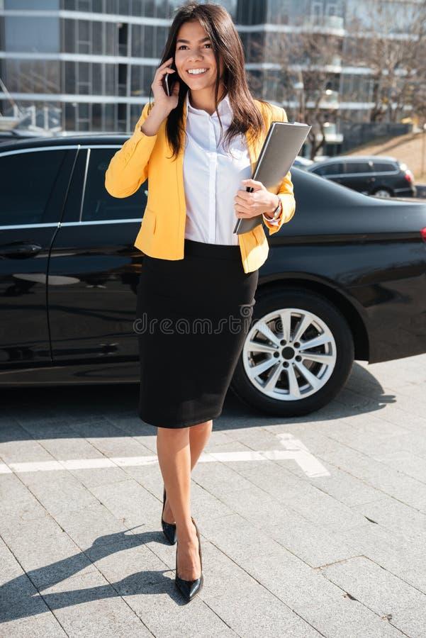 Nette junge Geschäftsfrau, die draußen am Handy geht und spricht stockbilder