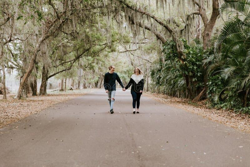 Nette junge glückliche liebevolle Paare, die hinunter eine alte verlassene Straße mit dem moosigen Eichen-Überhängen gehen stockbild