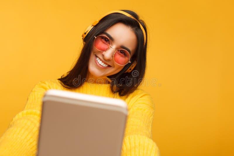Nette junge hispanische Frau, die ein selfie auf Gelb nimmt stockfotografie