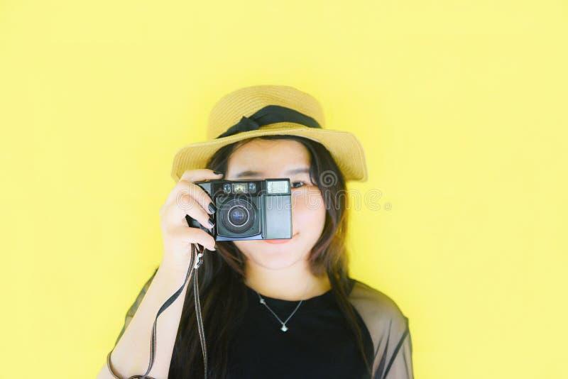 Nette junge lächelnde Asiatinporträtmode und Bildphotographen mit Weinlesefilmkamera auf gelbem Hintergrund nehmen stockfoto
