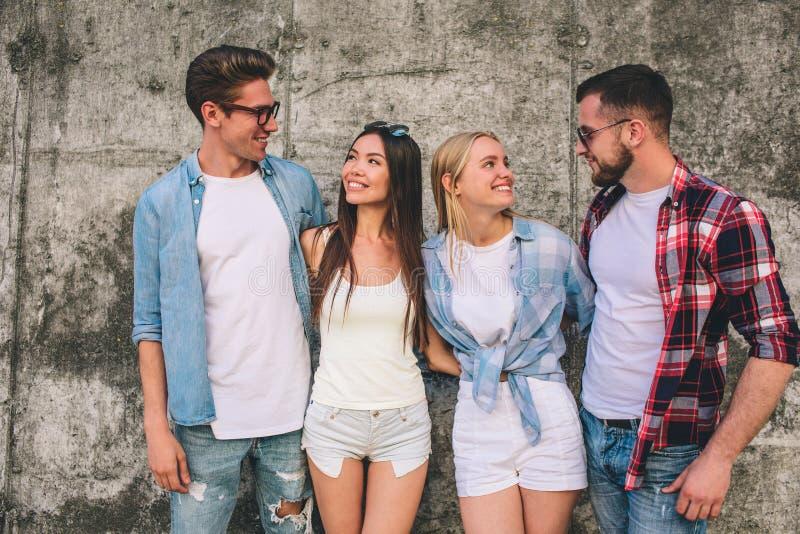 Nette junge Leute stehen zusammen auf grauem Hintergrund Mädchen betrachten Jungen und das Lächeln Kerlabnutzungsgläser und stockfotografie