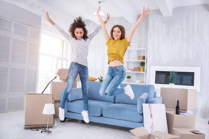 Nette junge Mädchen, die glücklich in neue Wohnung springen lizenzfreies stockbild