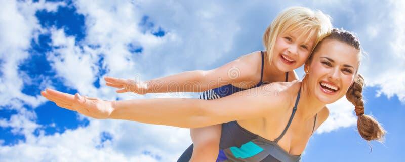 Nette junge Mutter und Tochter auf dem Strand, der Spaßzeit hat lizenzfreies stockbild
