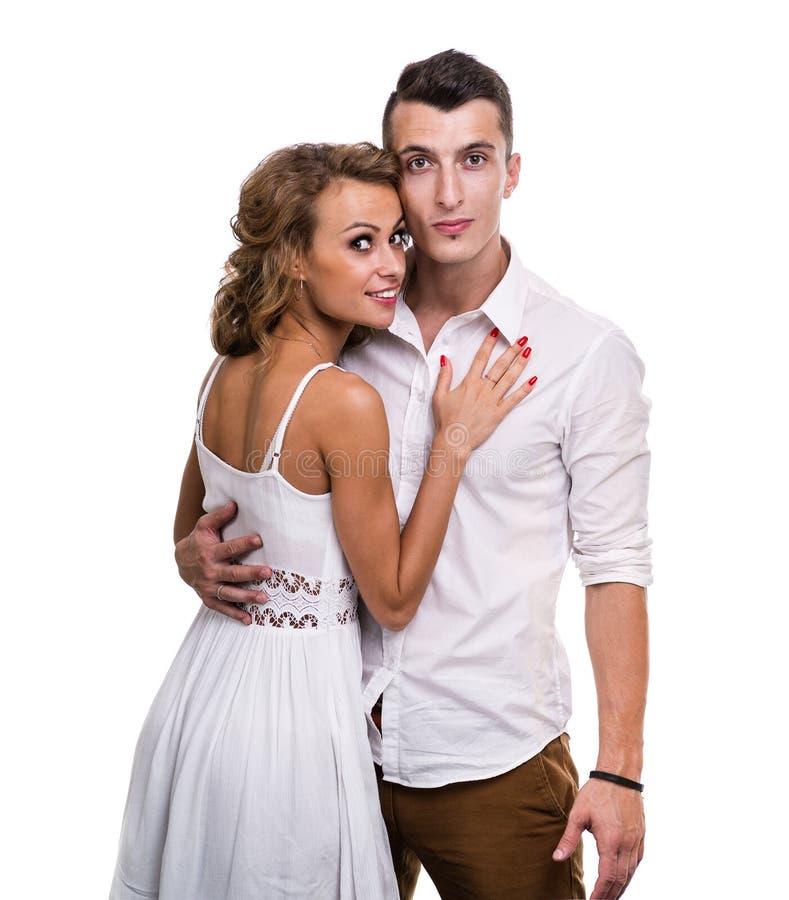 Nette junge Paare auf dem weißen Hintergrund, lokalisiert lizenzfreie stockfotografie