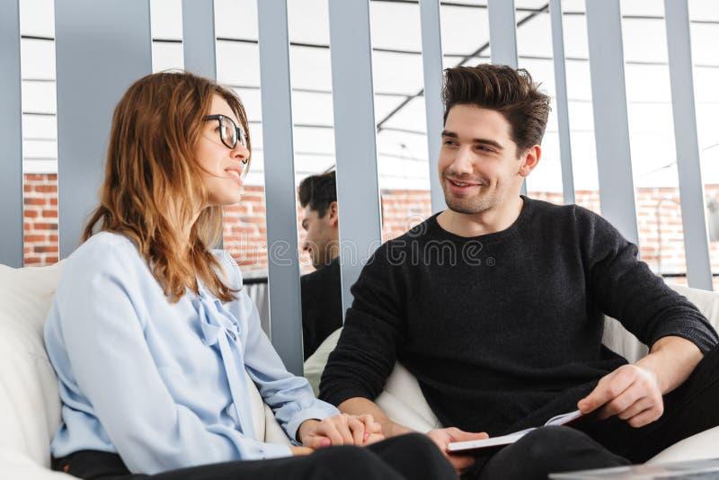 Nette junge Paare von den Kollegen, die zusammenarbeiten stockbild