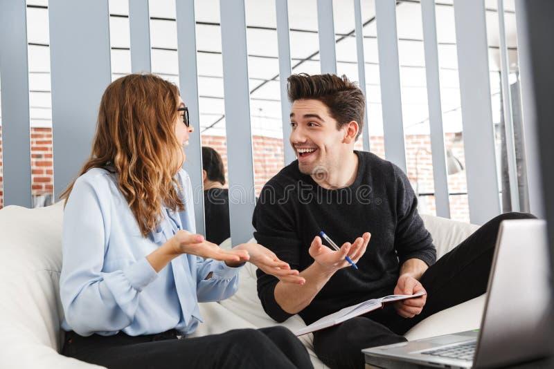 Nette junge Paare von den Kollegen, die zusammenarbeiten stockbilder