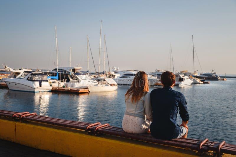 Nette junge schöne Paare, die zusammen am Pier am Hafen, Hippies sitzen und umarmen Rückseitige Ansicht stockbilder