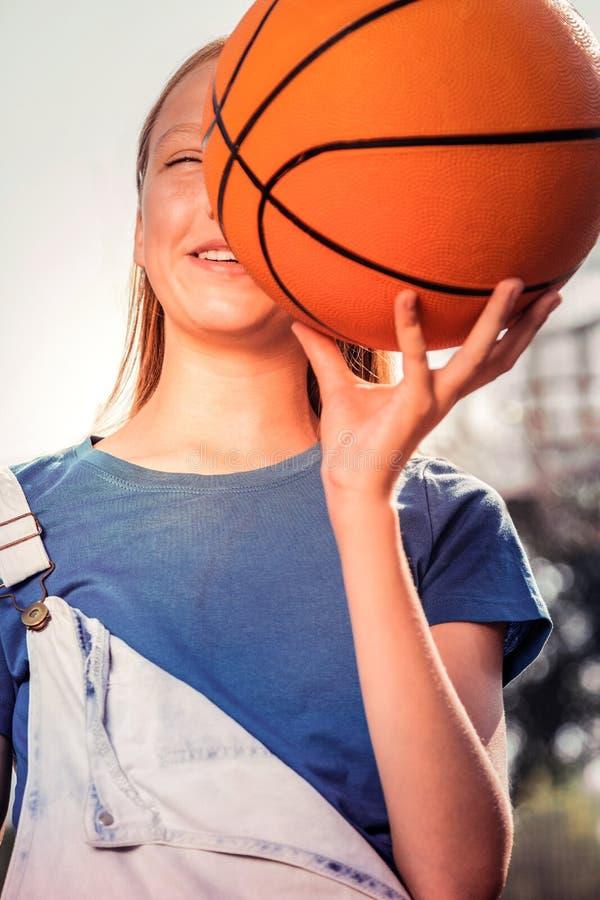 Nette junge sportive Dame in blaues T-Shirt tragendem Ball nahe ihrem Gesicht stockbild
