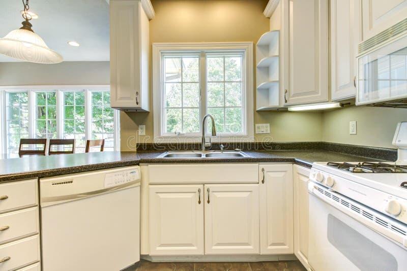 Nette Küche mit weißen Kabinetten und schwarzen Countertops lizenzfreie stockbilder