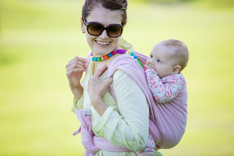 Nette kaukasische Frau, die im Frühjahr ihre Babytochter auf Park der Rückseite trägt lizenzfreie stockbilder