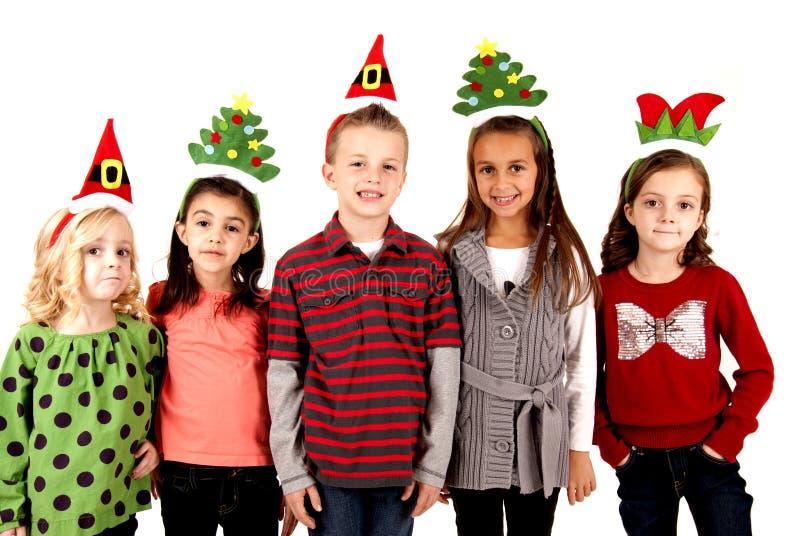 Nette Kinder in den lustigen Feiertagshüten stockfotografie