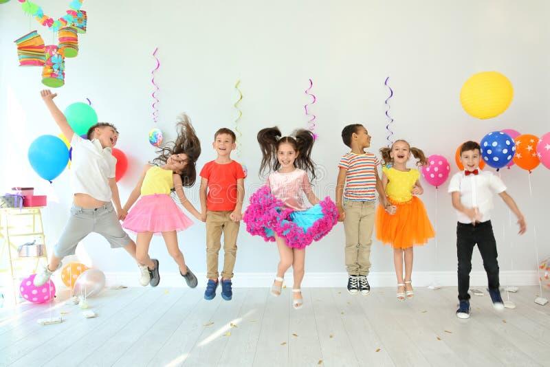 Nette Kinder an der Geburtstagsfeier zuhause lizenzfreie stockfotografie