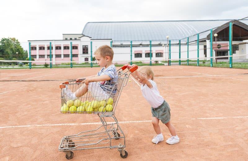Nette Kinder, die auf Tennisplatz spielen Wenig Junge und Tennisbälle im Einkaufswagen lizenzfreie stockbilder