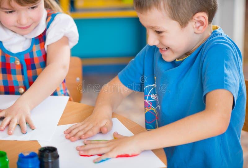Nette Kinder, die am Kindergarten malen stockbild